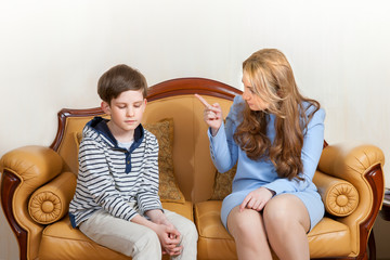 Mother scolds son, sitting on the sofa at home
