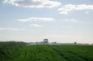Tractor spray field with chemicals and worker man