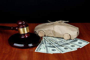 Gavel,model of car and money on table on black background