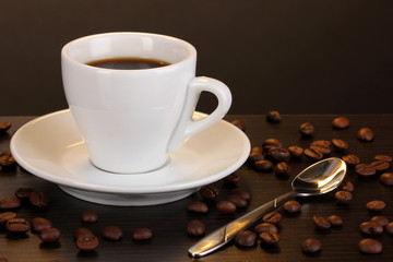 Cup of coffee on wooden table on brown background