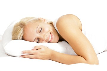 Light hair female model, smiling and lying on the pillow