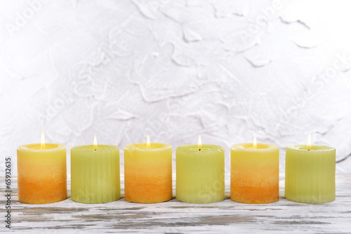 Beautiful candles on table on grey background