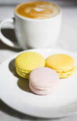 Plate Full of Delicious Macaroons at a Bakery with a Cup of Coff