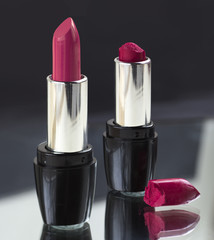 two red lipsticks, perfect versus imperfect symbolic concept ide