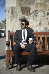 Indian Businessman having a break on bench with coffee.