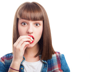 young woman eating popcorns on white background