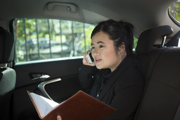 Asian business woman working in back of a car