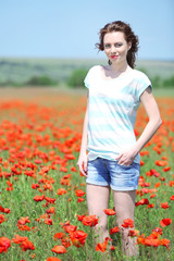 Beautiful young woman in poppy  field