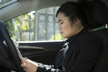 Chinese businesswoman reading newspaper in parked car.