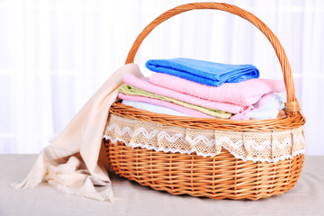 Colorful towels in basket on light background