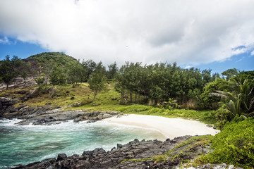 Small sandy beach between frozen lava flows of tropical volcanic