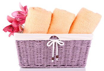 Color towels and lily flowers in wicket basket, isolated