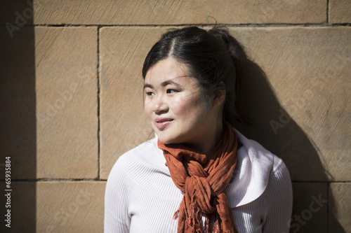 Fotobehang Muziek Portrait of a Asian woman leaning against a wall.