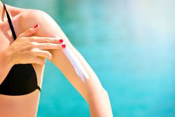 Close up of a female applying suncream.