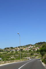 Strada asfaltata con curve e piccolo villaggio