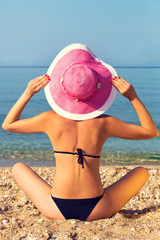 Young woman,holding pink hat,by the sea.