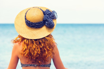 Curly haired woman,wearing sun hat,looking at the sea.