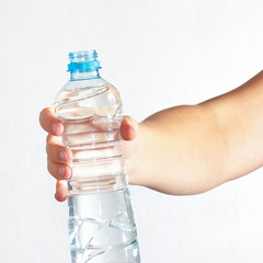 Female hand holding a bottle of fresh water