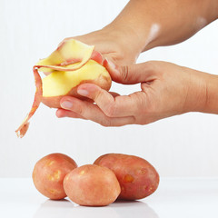 Hands peeling fresh potatoes on a white background
