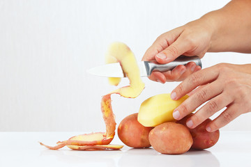 Hands peeling fresh potatoes with a knife