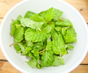 Pepper mint leaves in small cup on old wood background