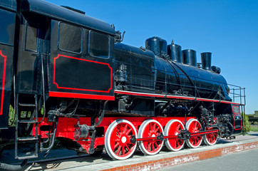Old Russian (Soviet) steam locomotive on a pedestal on a backgro