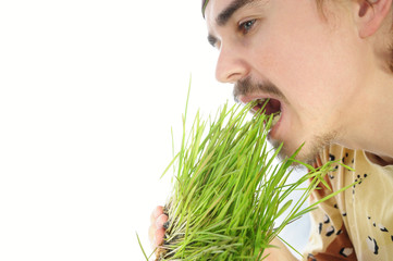 Young man biting green grass