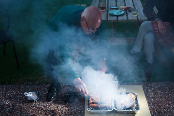Senior man cooking on a barbecue