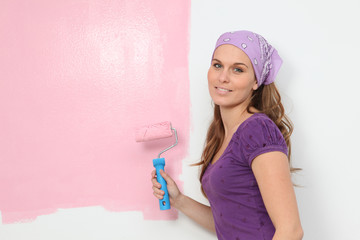 woman painting baby nursery pink