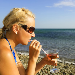 Girl drinks from tubule on beach
