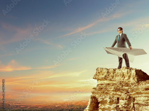 Businessman flying on paper plane - 65941403