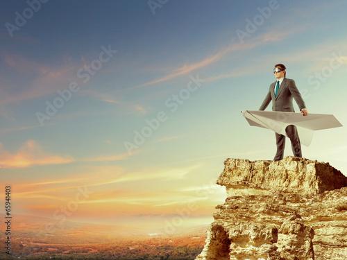 Leinwandbild Motiv Businessman flying on paper plane