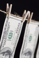 Hundred Dollar Bills Hanging From Clothesline on Dark Background