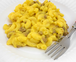 A close view mac and cheese with meat and fork on plate.