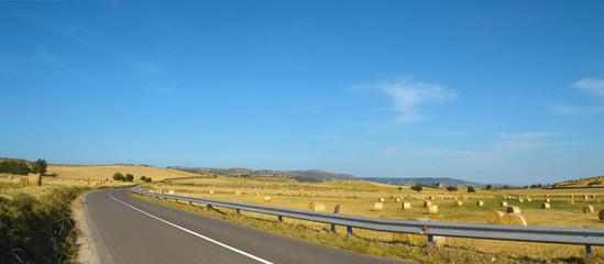 Strada asfaltata con colline e rotoballe