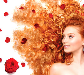 Beauty girl with long curly red hair and beautiful red roses