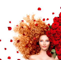 Beauty woman with long curly red hair and beautiful red roses