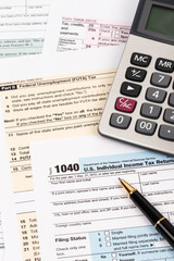 Tax form with pen and calculator taxation concept