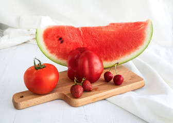 Water melon, tomatoes, strawberries and cherries on wooden backg