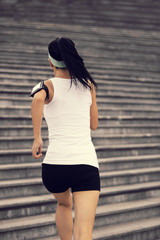 woman running listening to music in headphones from smart phone