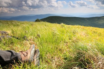 Legs of resting tourist in the mountain landscape.
