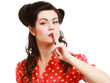 Retro. Pinup girl with finger on lips asking for silence