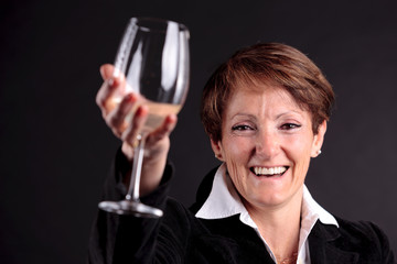 pretty old woman rising up a glass of wine (focus on face)