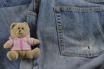 放在牛仔裤上的玩具熊