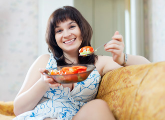 Happy ordinary woman eats vegetables
