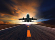 Leinwanddruck Bild - passenger jet plane flying over airport runway against beautiful