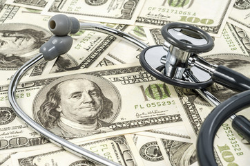 Close up stethoscope  and Bunch of US dollars as a background
