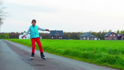 Happy young girl riding on roller blades