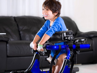 Disabled biracial boy in medical walker. Living room setting.