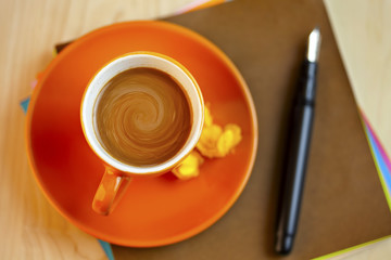 Orange coffee cup on brown writing paper with pen